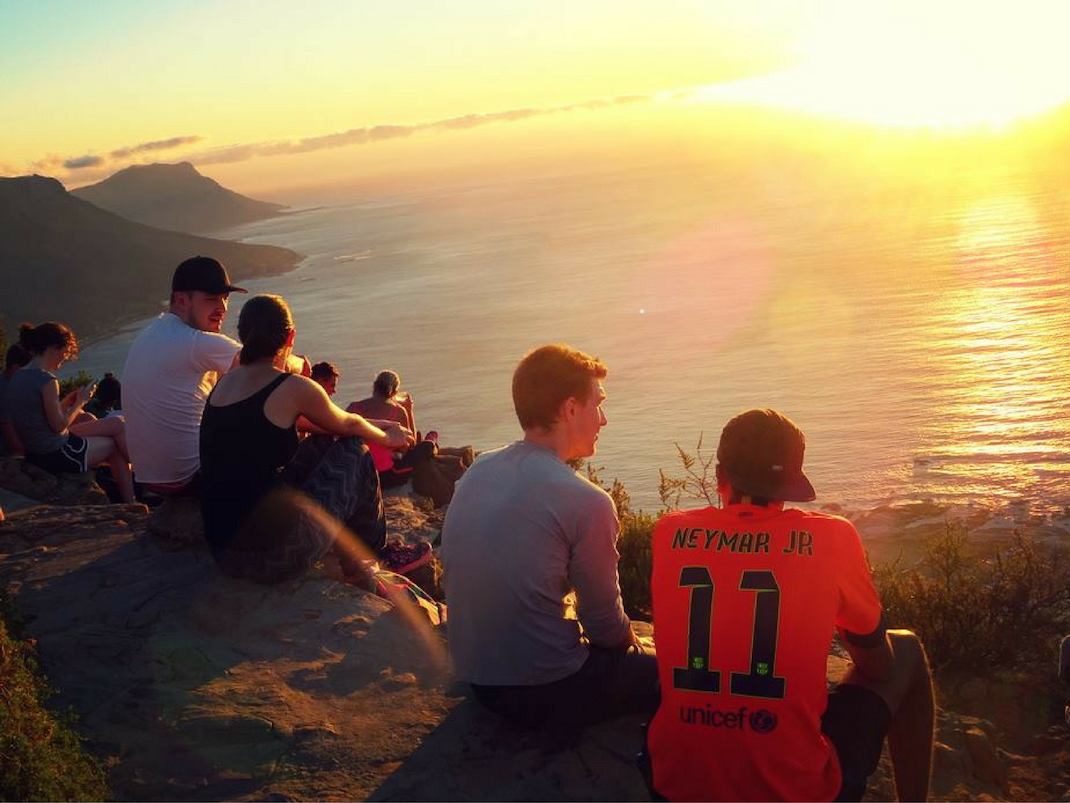 Internship students watch the sun set on Lions Head Cape Town
